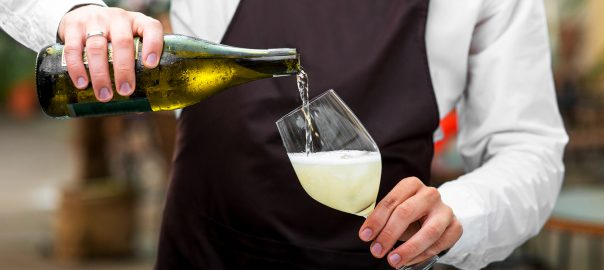 Barman pouring sparkling wine to the glass on the dark apron background